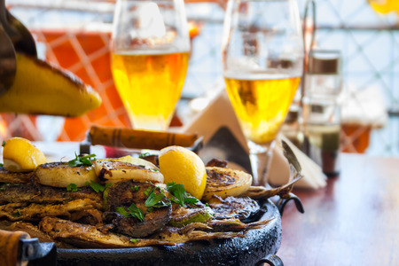 Bulgarian national dish with two glasses of beer. hot plate with fish, courgettes and onions in a lemon sauce. Shallow depth of field