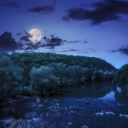wild river flowing near the camping in  forest at the foot of mountain at night in moon light Stock Photo