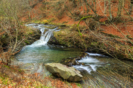 incredibly beautiful and clean little river with several cascades over large stones in the forest Stock Photo