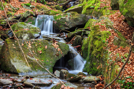 incredibly beautiful and clean little waterfall with several cascades over large stones in the forest comes out of a huge rock covered with moss