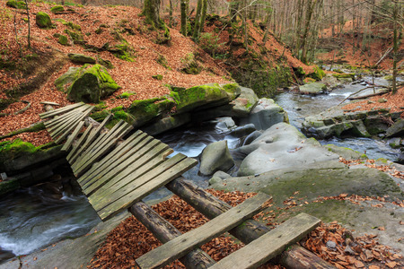 old broken bridge of planks over the river with stones and moss in the forest near the mountain slope