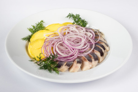 potato and onion  circles with marinated herring in white plate on white background