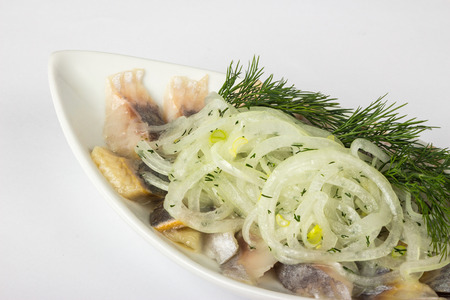 onion circles and dill with marinated herring in white plate on white background Stock Photo