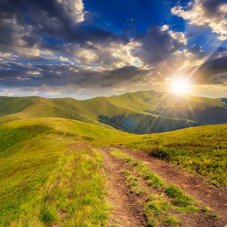 brede weg in de buurt van het gazon in de hoge bergen bij zonsondergang