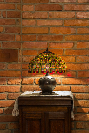 table lamp of stained-glass on old wooden stand on red brick wall background