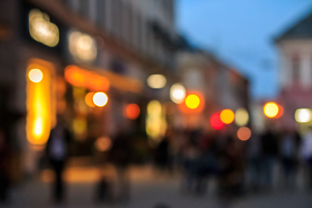 A crowd of people moving on the old european city night street defocused blurred abstract image