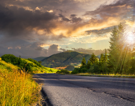 asphalt road going to high mountains down the hill and  passes through the green shaded forest at sunset Stock Photo