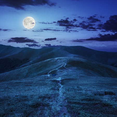 small lake near mountain curve path on a Green Hill at night in full moon light