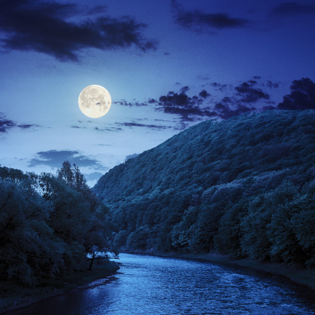 fool moon: river flowing between green mountains through the forest at night in fool moon light