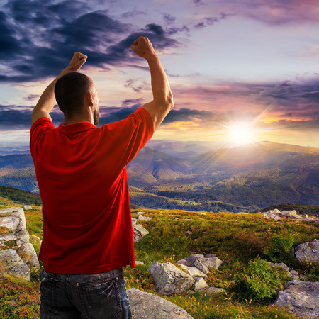 man in red shirt standing in sunlight on stone mountain slope with forest at sunset Stock Photo