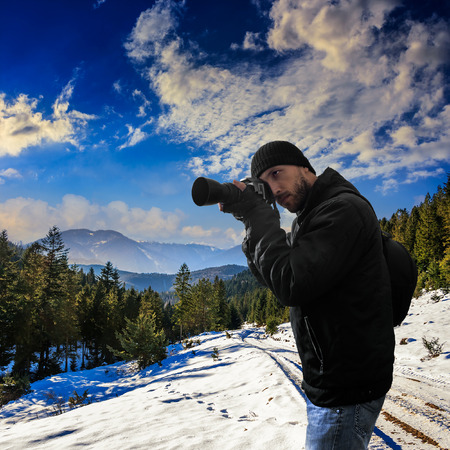 young photographer with camera and bag stands on snowy road to coniferous forest in mountains on sunrise