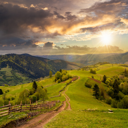 autumn path: autumn landscape. fence near the meadow path on the hillside. forest in fog on the mountain. Stock Photo