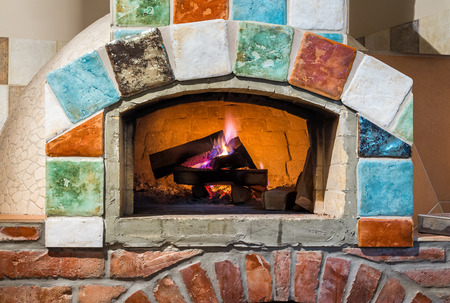 burning fire in professional stone-hearth pizza oven with Italian style tiles