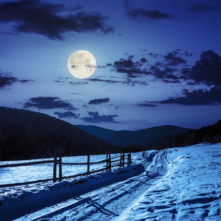 winter mountain landscape. winding road that leads into the pine forest covered with snow. wooden fence stands near the road at night in full moon light