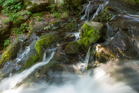 incredibly beautiful and clean waterfall with several cascades over large stones in the forest comes out of a huge rock covered with moss. view from above