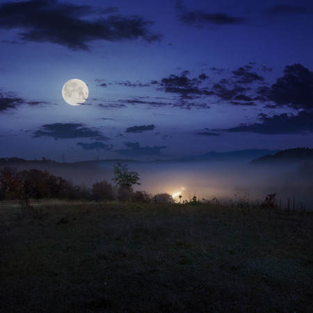 car lights in cold morning fog before  sunrise near the village in mountains  in autumn at night in full moon light Stock Photo
