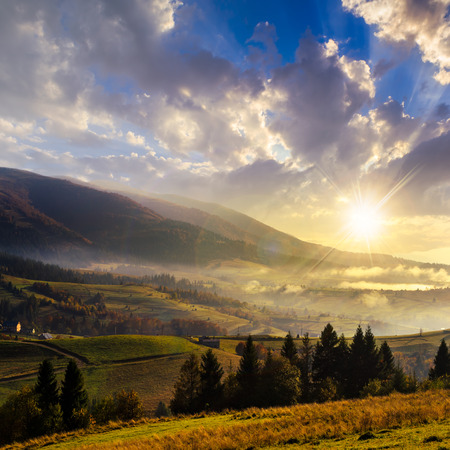 autumn landscape. village on the hillside. forest on the mountain light fall on clearing on mountains at sunset photo