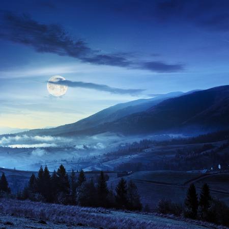 fool moon: autumn landscape. village on the hillside. forest on the mountain light fall on clearing on mountains at night in fool moon light