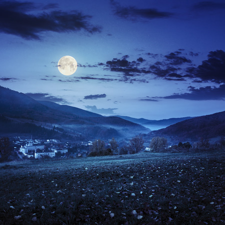 fool moon: autumn landscape. village on the hillside. forest in fog on mountains at night in fool moon light