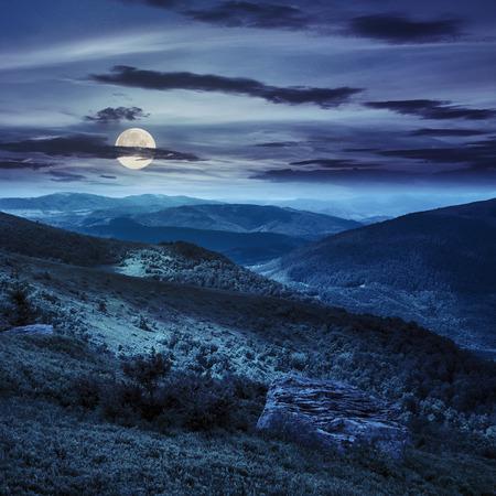 山の風景。丘の中腹に石が付いている谷。満月の光で夜に丘の上で光のビームの下で山の森