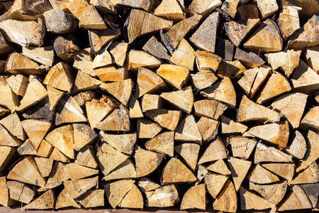 Yellow dry chopped conifer firewood logs background in a pile outdoor in sunlight