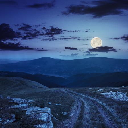 full: road among white sharp stones on the hillside on top of mountain range at night in full moon light
