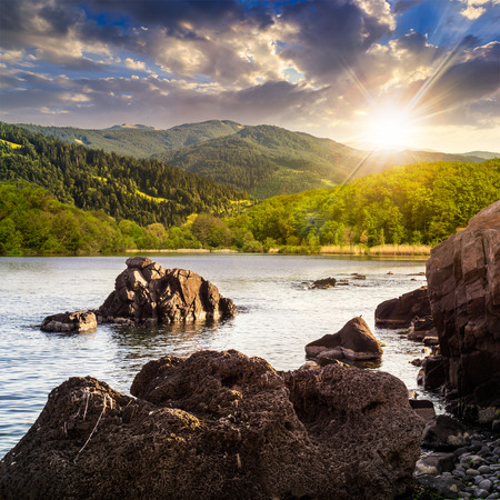 view on lake with rocky shore and some boulders near forest on mountain  with high vista far away in sunset light