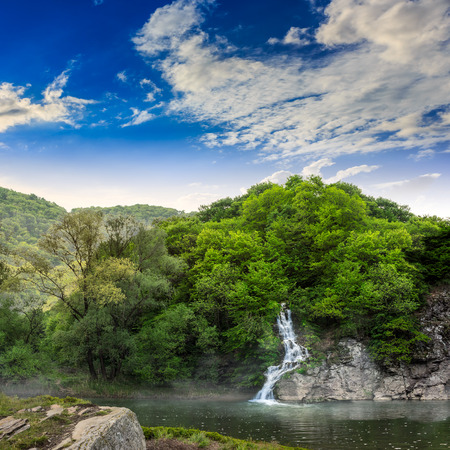 small waterfall comes out of a forest on a rocky hill and falls in river with fog Stock Photo