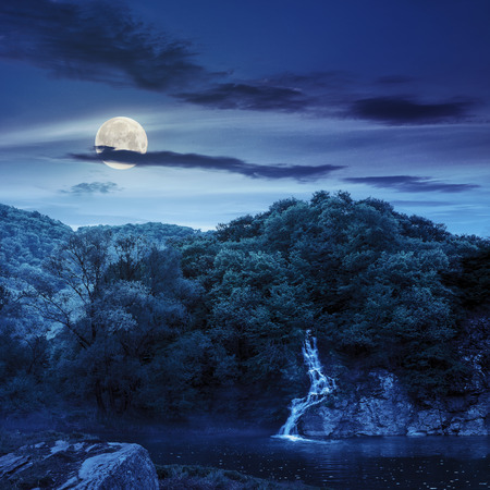 small waterfall comes out of a forest on a rocky hill and falls in river with fog at night in full moon light Stock Photo - 34459781