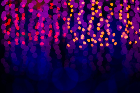 abstract background of blurred warm yellow and red lights with cool blue and purple background with bokeh effect