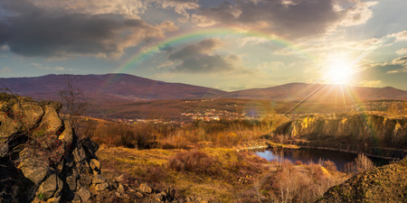 collage of small lake in an abandoned stone quarry in the mountains outside the city in sunset light with rainbow Stock Photo