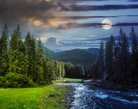 コラージュ、昼と夜の山と前に満月の湖に流れる川で松の木のある風景