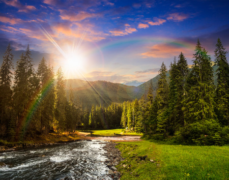collage landscape with pine trees in mountains and a river in front flowing to lake in sunset light with rainbow Stock Photo