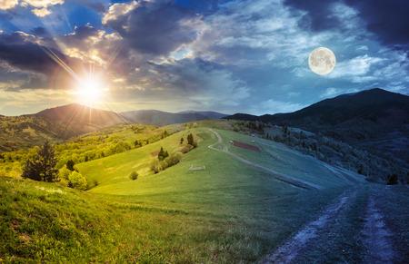 昼と夜の風景をコラージュします。丘の上の草原パス近くのフェンス。太陽と満月と山の森近くの村 写真素材
