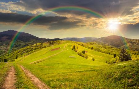 風景をコラージュします。丘の上の草原パス近くのフェンス。虹と夕日の光の山の森の近くの村