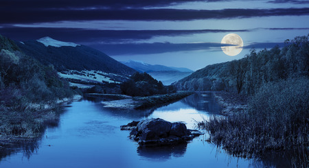 composit: collage mountain river with stones and grass in the forest near the mountain slope at night in full moon light Stock Photo