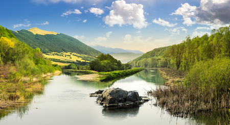 composit: collage mountain river with stones and grass in the forest near the mountain slope in sunrise light