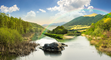 composit: collage mountain river with stones and grass in the forest near the mountain slope in sunrise light with rainbow