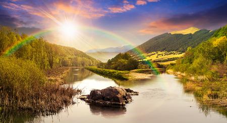 石の山の川のコラージュし、虹と夕日の光の中で山の斜面の近くの森の草