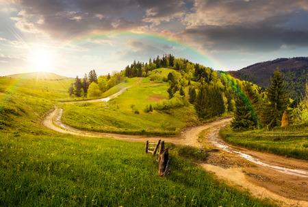 composiet herfst landschap. hek in de buurt van het kruispunt op de heuvel weide in de bergen. enkele dennenbomen bos aan beide zijden van de weg in zonsondergang licht met regenboog