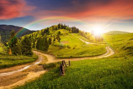 複合の秋の風景。山の中腹草原の交差道路の近くのフェンス。虹と夕日の光の中で道路の両側の森のいくつかのモミの木 写真素材