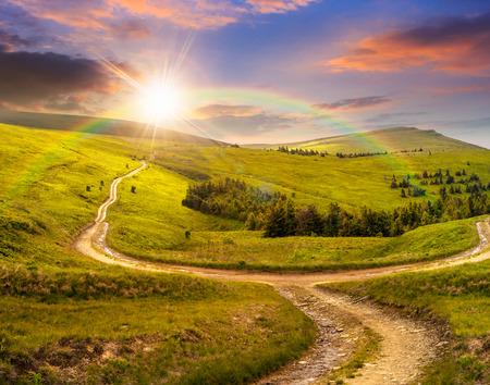 composiet herfst landschap. hek in de buurt van het kruispunt op de heuvel weide in de bergen. enkele dennenbomen bos aan de zijkanten van de weg in zonsondergang licht met regenboog