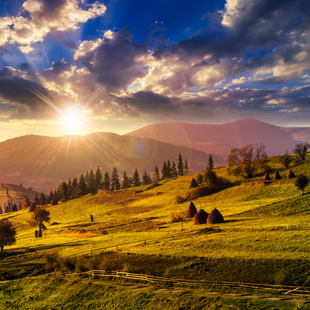 composte landscape with path near haystack  on a green meadow in the mountains in sunset light Stock Photo