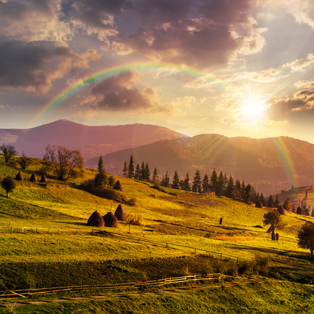 composte landscape with path near haystack  on a green meadow in the mountains in sunset light with rainbow Stock Photo