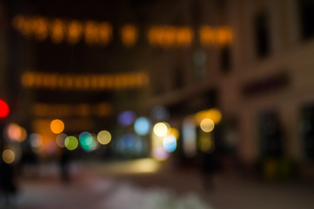 people moving on the old european city winter night street defocused blurred abstract image Stock Photo