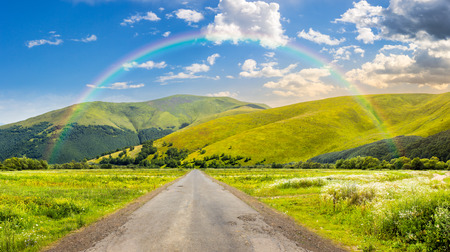 composite landscape with abandoned asphalt road rolls through meadows with flowers going to high  mountains in morning light with rainbow