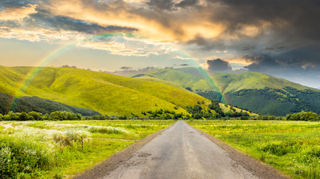 composite landscape with abandoned asphalt road rolls through meadows with flowers going to high  mountains with rainbow Stock Photo