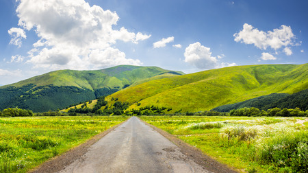 composite landscape with abandoned asphalt road rolls through meadows with flowers going to high  mountains Stock Photo