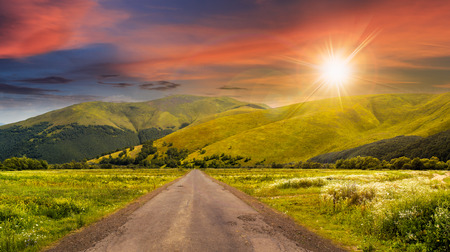 composite landscape with abandoned asphalt road rolls through meadows with flowers going to high  mountains in sunset light Stock Photo