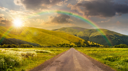 composite landscape with abandoned asphalt road rolls through meadows with flowers going to high  mountains in sunset light with rainbow